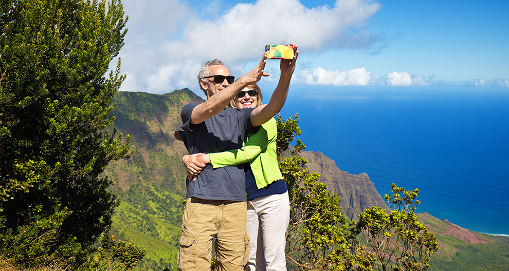 a man 和 women take a selfie on a mountainside overlooking a deep blue sea